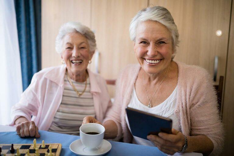 Proveer Senior Living | Senior Women Smiling With Tea & a Tablet