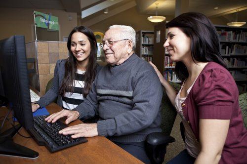 Proveer Senior Living   Senior man using computer with associates